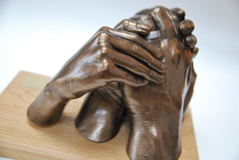 3D free-standing bronze family hand casting on wooden plinth and plaque